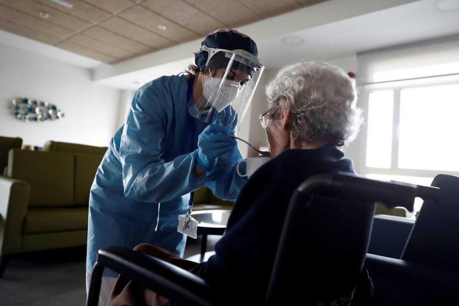 Una cuidadora dona de menjar a una dona gran en una residència