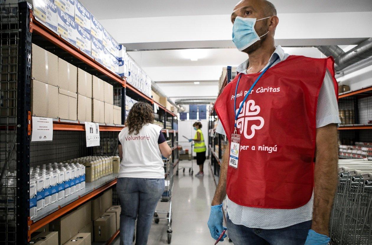 Treballadors de Càritas en un local de repartiment d'aliments