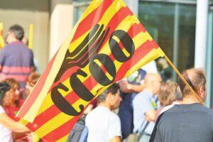 Un manifestante lleva una bandera de CCOO