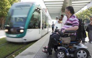 Un hombre en silla de ruedas espera en el andén para subir al TRAM