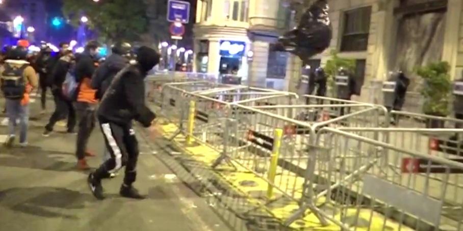 Un encaputxat llança una bossa d'escombraries contra la comissaria de la Via Laietana