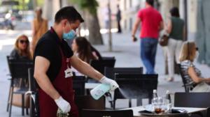 Un cambrer netejant una taula