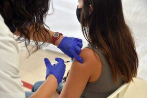 Sanitaria vacunando a una joven